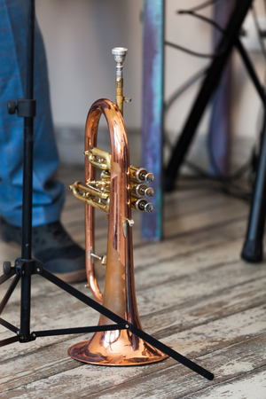 Vintage trumpet stands on grungy wooden floor. It is a brass instrument commonly used in classical and jazz ensembles