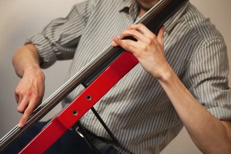 Hands of a man playing red modern electric contrabass in musical studio