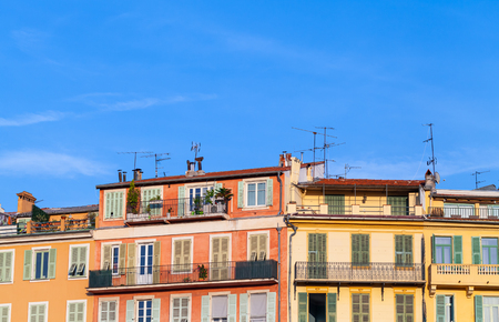 Facades of traditional old living houses under blue sky. French Riviera, Nice, France