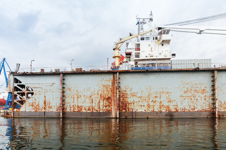 Old rusty floating dry dock with ship under repair inside