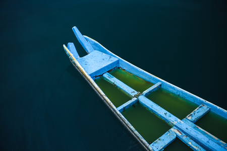 Bow of an old blue wooden Chinese fishing boat with water inside