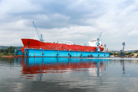 Red tanker is under repairing in blue dry dock of Varna shipyard, Bulgaria