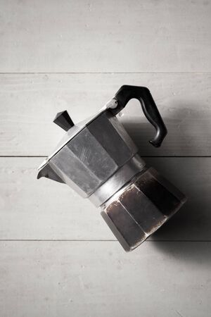 Vintage moka pot lay on white wooden table. It is a old stove-top coffee maker that brews coffee by passing boiling water pressurized by steam through ground coffee
