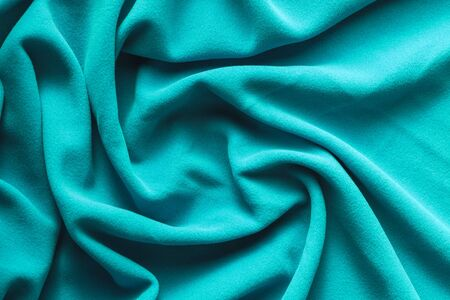 Background texture of cyan fleece, soft napped insulating fabric made of polyester, wavy pattern, top view