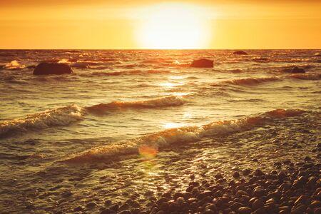 Paysage côtier de la mer Baltique au coucher du soleil avec des eaux de rivage orageuses et des pierres. Filtre de correction tonale chaude