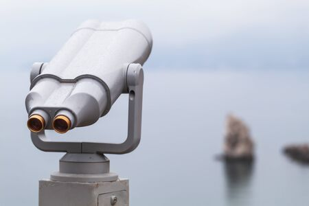 Binocular telescope on a rotating base mounted on an outdoor touristic viewpoint. Close up photo with blurred seascape on a background