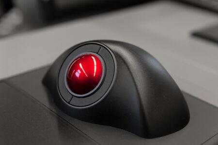 Panel de control industrial con trackball rojo, foto de primer plano con enfoque selectivo suave