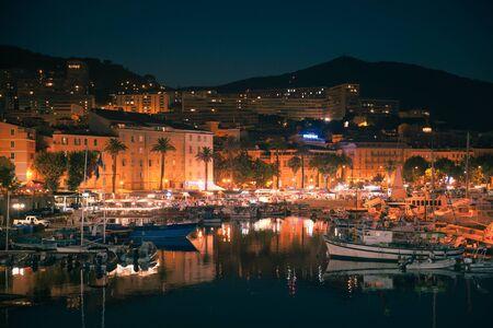 Ajaccio, France - July 6, 2015: Night view of Ajaccio city. Pleasure yachts and motor boats moored in marina. Corsica island