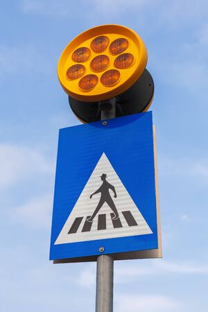 Pedestrian crossing. Road sign with schematic walking man and yellow warning lights over blue sky Stock fotó
