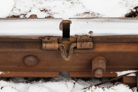 Gap between rusted rails. Close-up railway details photo with selective focus