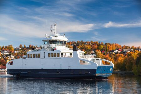 Passenger ferry enters the port of Norwegian town at sunny autumn day. Levanger, Norway