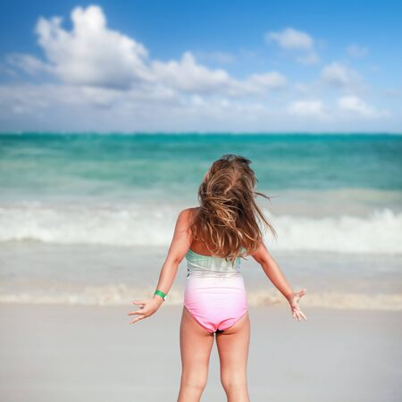 Happy blond baby girl in green and pink swimsuit stands on the ocean coast under cloudy sky at sunny day, rear view Imagens