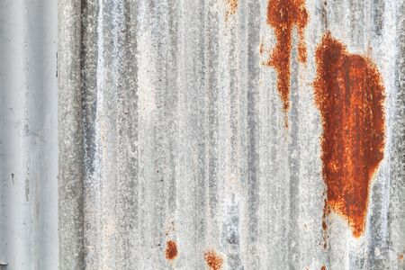 Old gray corrugated metal wall with rust spots, frontal background photo texture