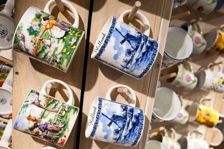 Zaanse Schans, Netherlands - February 25, 2017: Ceramic mugs with decorative Dutch paintings hang on wooden counter in tourist souvenir shop Редакционное