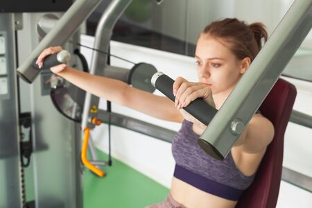 Young beautiful blond sporty girl does machine chest press exercising in a gym