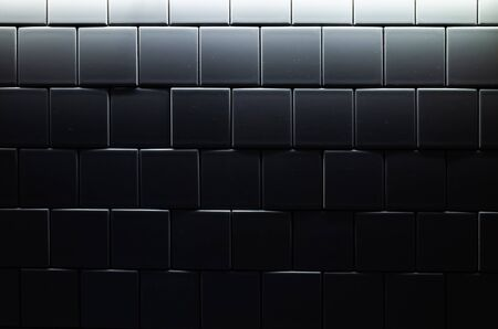 Tiled wall in dark room with blue illumination, background photo texture