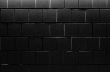 Tiled wall in dark room with poor illumination, background photo texture