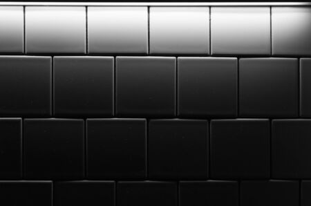 White tiled wall in dark room with poor illumination, background photo texture