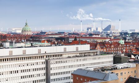 Copenhagen, Denmark. Modern cityscape with wind turbines and power plant on a background