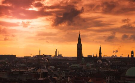 Dark silhouette skyline of Copenhagen city under colorful evening sky. Photo taken from The Round Tower, popular old city landmark and viewpoint. Denmark