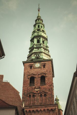 Nikolaj Kirke or Nikolai Church located in old town of Copenhagen, Denmark. Vintage toned photo with retro tonal correction filter effect