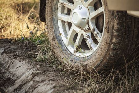 Muddy SUV car wheel is on rural roadside, close up photo, off-road racing theme