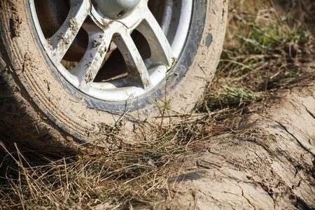Dirty 4x4 SUV car wheel with light alloy disc is on rural roadside with grass, close up photo, off-road racing theme Stock fotó
