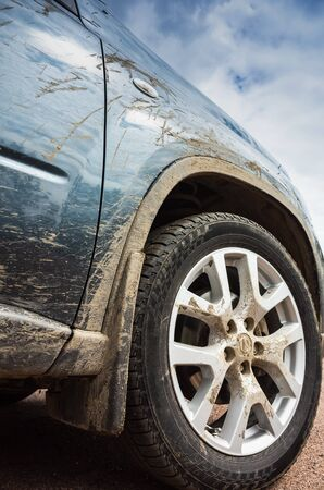 Dirty SUV car stands on rural road, Wheel with light alloy disc close up photo. Off-road racing vertical photo