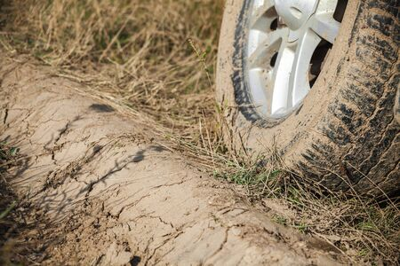 Dirty car wheel is on wet rural roadside with grass, close up photo, off-road racing theme