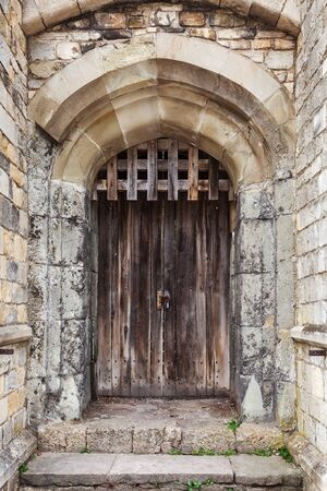 Locked wooden door in old fortification wall, background photo texture