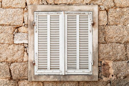 Old window with closed white wooden shutters in ancient stone wall, front view, background photo texture