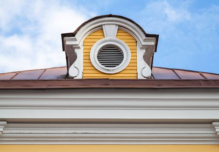 Vintage attic ventilation window on a roof slope in decorative round white wooden frame Stock fotó