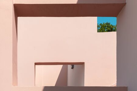 Abstract contemporary architecture photo, niches in pink painted concrete walls under blue sky