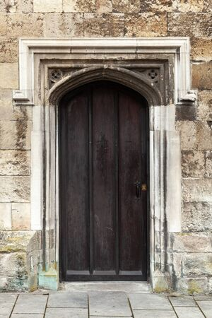 Closed black wooden door in old stone wall, vertical background photo texture