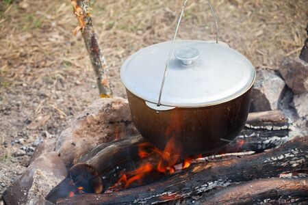 Bonfire and black cauldron. Preparing of a soup on open fire, camping meal