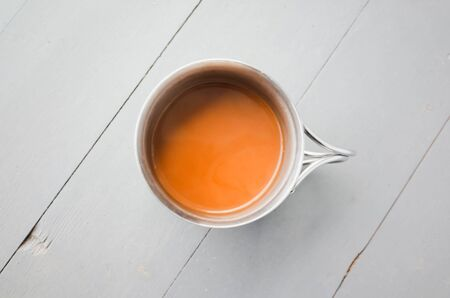 Steel mug of coffee with milk stands on a white wooden table, closeup top view photo with selective focus
