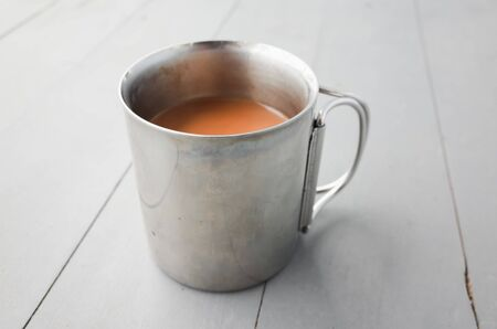 Metal mug of coffee with milk stands on a white wooden table, closeup photo with selective focus Фото со стока