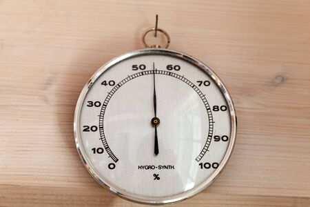 Analog Hygro Synth hygrometer hanging on wooden wall, close-up photo. This hair tension instrument used to measure the amount of humidity and water vapour in the atmosphere