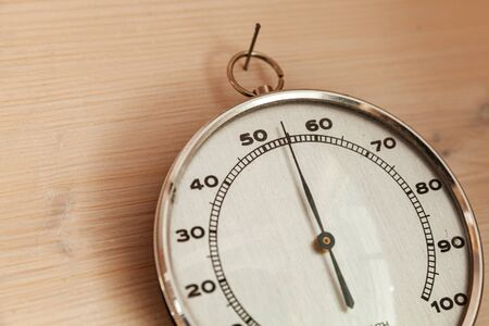 Analog hygrometer hanging on wooden wall, close-up photo. This hair tension instrument used to measure the amount of humidity and water vapour in the atmosphere 版權商用圖片