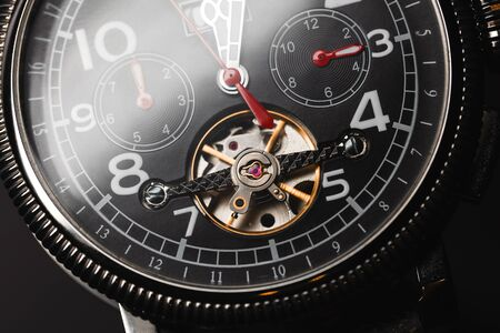 Mechanic luxury wrist watch with automatic winding and red arrows, close-up fragment