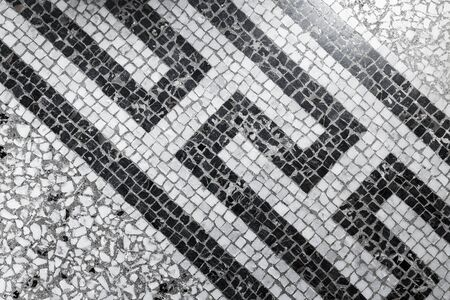 Ancient stone mosaic floor tiling with black and white geometric pattern, background photo texture