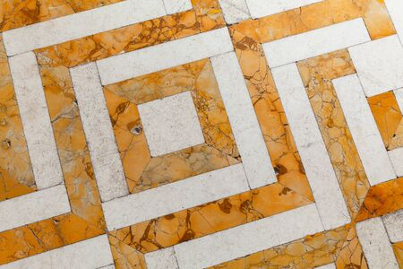 Retro style stone mosaic floor tiling with yellow white geometric pattern, background photo texture