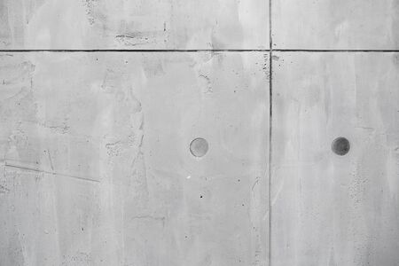 New gray concrete wall fragment with joints and technological holes, close-up background photo texture