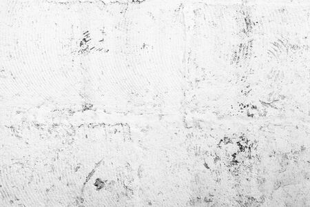 Grungy concrete wall with cracked white paint layer, background photo texture