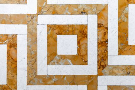 Vintage stone mosaic floor tiling with yellow white geometric pattern, top view, background photo texture