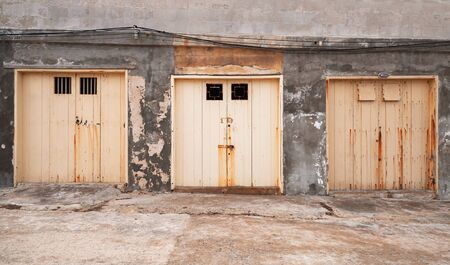 Three closed yellow gates in a row in grungy concrete wall, old port building facade, front view