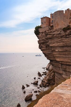 Old stone houses on a cliff. Coastal landscape of Bonifacio. Corsica island, France. Vertical photo