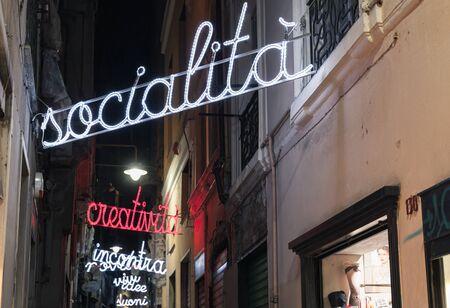 Genova, Italy - January 17, 2018: Night street of Genova, illuminated advertising texts