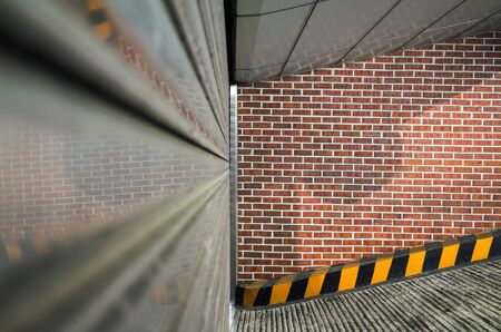 Abstract urban  with closed underground garage door and red brick wall
