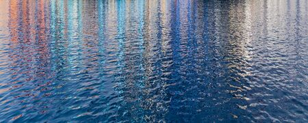 Abstract rippled water surface, wide background photo with bright colorful reflections 免版税图像